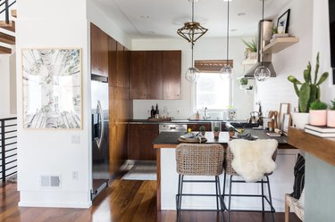 Eclectic bohemian kitchen lighting with wood cabinets and black countertops
