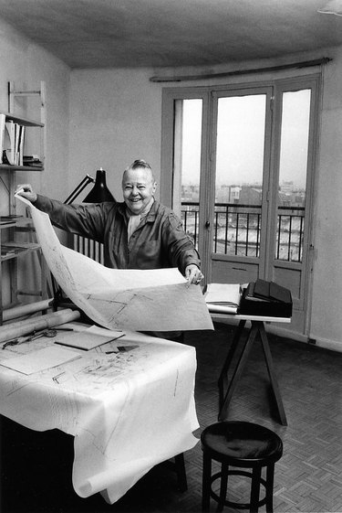photograph of Charlotte Perriand holding a large sheet of paper