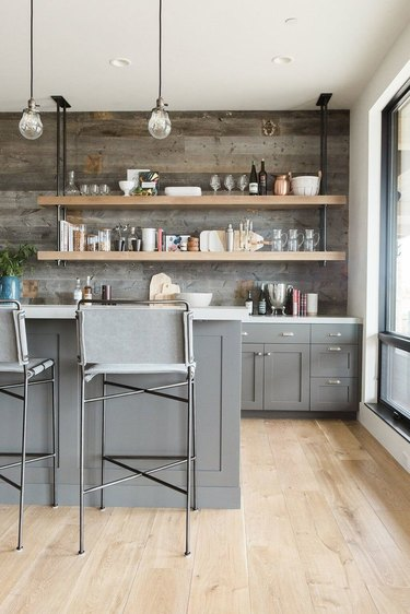 industrial pipe shelving above wet bar