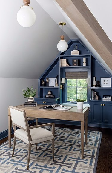 Attic apartment with deep blue wall, built-in shelves, desk, chair, patterned rug, white globe pendant lamps.