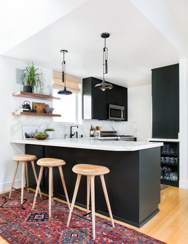 Black bohemian kitchen lighting over white marble countertop with black cabinets
