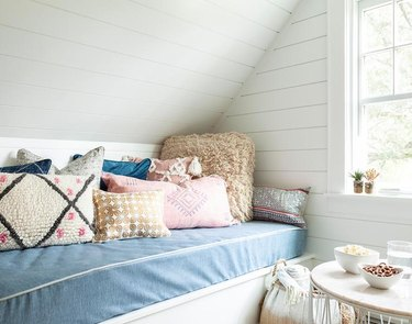 built-in bench in attic playroom with white shiplap and patterned throw pillows