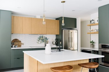 green kitchen cabinets and wood cabinets with marble countertop and backsplash