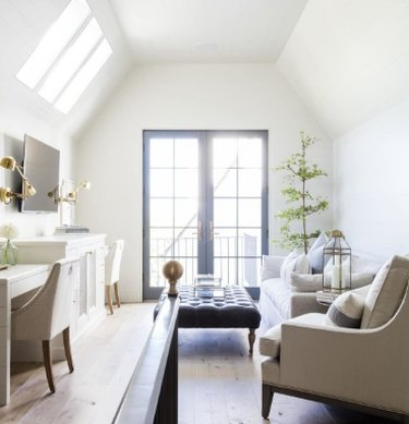 attic apartment with skylights, neutral chairs, black leather ottoman, french doors, wood floors, plant.
