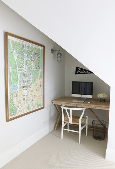 attic apartment nook with small wood desk, wood chair, computer, map on wall.