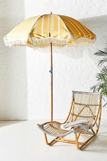 yellow beach umbrella with fringe tassel and stripes