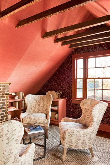 attic apartment with red-orange wallpaper, patterned wallpaper, wood beams, high back chairs, patterned rug.