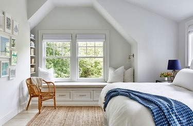 attic apartment with window seat, cane chair, white walls, white bedding, blue throw.