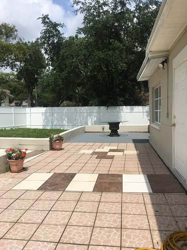 Patio before and after with a stenciled concerete floor and string lights