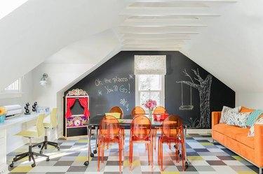 attic playroom with chalkboard wall, orange chairs, and orange sofa