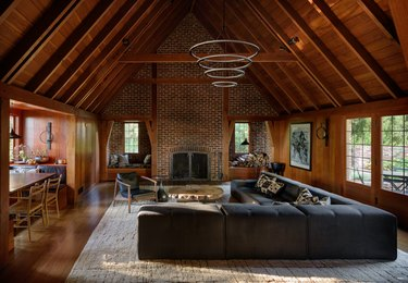 Wood beamed a-line ceiling, black sectional, modern pendant light, and brick fireplace in attic apartment
