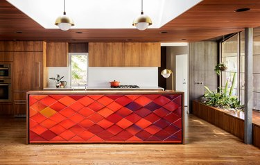 midcentury kitchen island idea with red tile back panel and wood cabinets