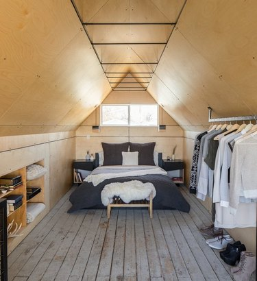 attic apartment with rustic wood floors, plywood walls, wardrobe rack, open shelves, gray bedding.