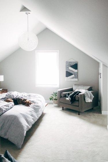 Attic bedroom idea with white, minimal decor and white circular pendant light
