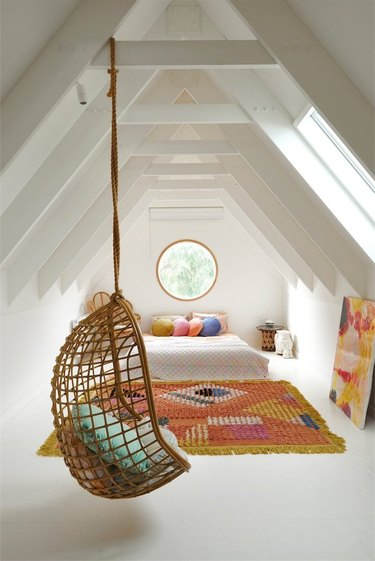 Attic bedroom idea with colorful area rug and rattan hanging chair