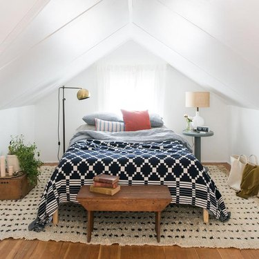 Attic bedroom idea with white walls and bed with navy and white comforter