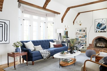 navy blue living room idea by Emily Henderson with tufted blue sofa and brick fireplace