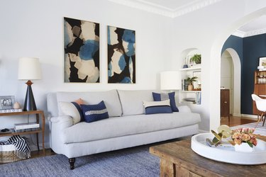 navy blue living room idea designed by Emily Henderson with blue accent pillows on sofa