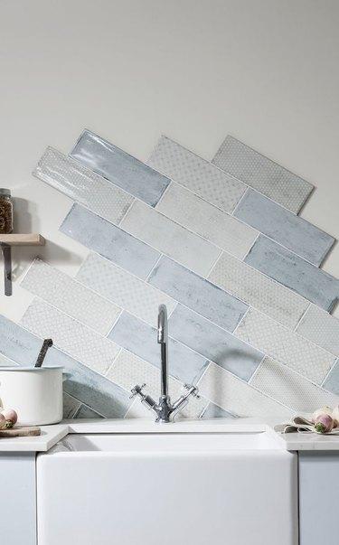 unfinished blue and white kitchen backsplash with farmhouse sink