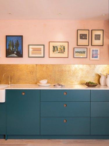 gold metallic kitchen backsplash with blue cabinets and pink walls