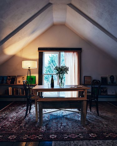 small attic library with floating shelves and table