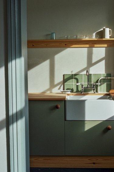 minimal sage green kitchen backsplash with green cabinets and wood countertop