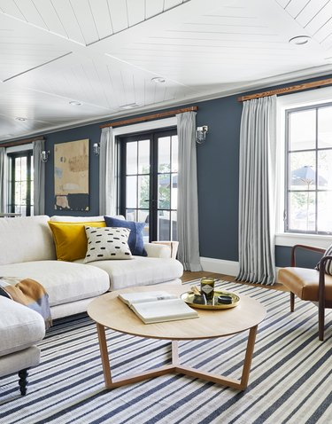 navy blue living room idea designed by Emily Henderson with striped area rug and floor-to-ceiling drapery