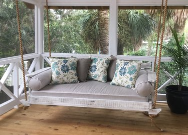coastal furniture on an enclosed porch surrounded by palm trees