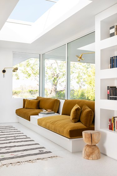 Velvet mustard yellow cushions on built-in sofa next to windows flanked by brass wall sconces
