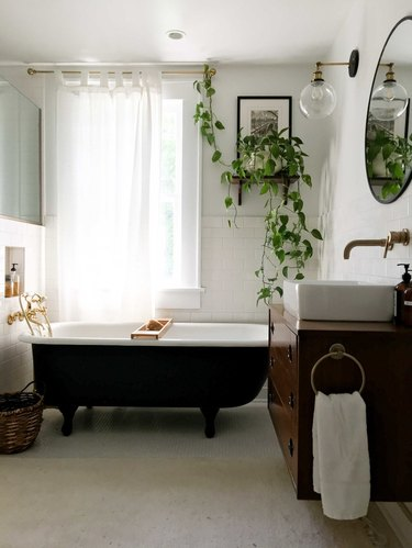 vintage bathroom lighting idea with midcentury wall sconce and clawfoot bathtub