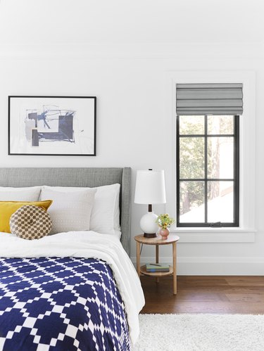 Bedroom with mustard yellow accent pillow and upholstered gray headboard and wooden side table