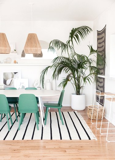 white bohemian dining room with green chairs and woven pendant lights