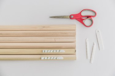 Stick sandwiched pairs of picture hanging strips to the top and bottom edges of the dowels.