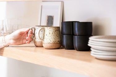 Ceramic mugs on open shelf