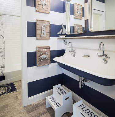 coastal bathrooms with blue and white striped walls, trough sink, nautical themed artwork, foot stools.