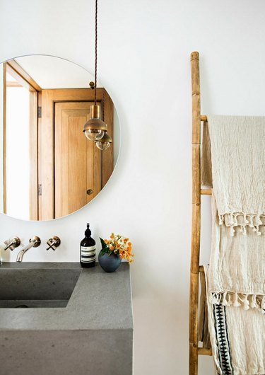 small bathroom lighting idea with mini pendant at vanity near round mirror on the wall and concrete sink