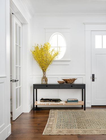 Mustard yellow foliage styled in an entryway on top of black console table with shelf for storage