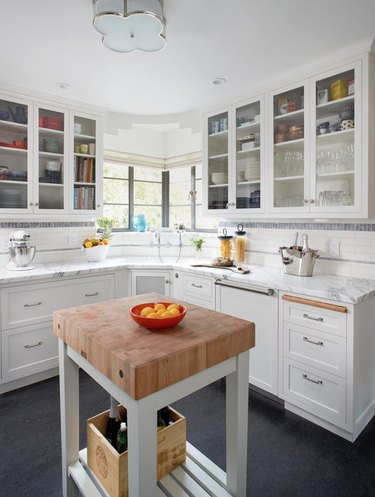 Blue linoleum kitchen flooring with small island topped with butcher block and white cabinets