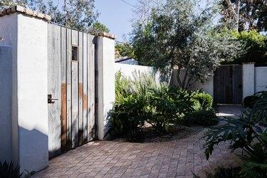 a decorative brick garden path in a Spanish-style home's backyard