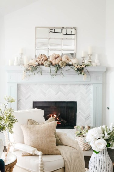 Fall decor idea for living room with pumpkins and greenery on mantel in white living room