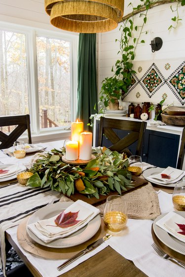 Fall centerpiece with green leaves and candles in bohemian dining room