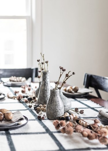 Gray vase fall centerpieces with dried florals and plaid tablecloth