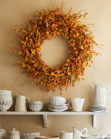 fall wreath made with forsythia hanging above a shelf with dishes
