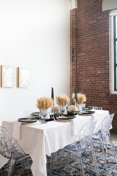 Dried wheat fall centerpieces with black candles in modern dining room