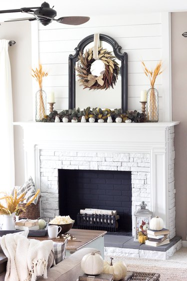 Fall decor idea for fireplace with dried wheat, greenery, and wood candleholders