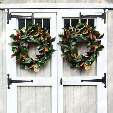 two magnolia leaf fall wreaths on barn doors