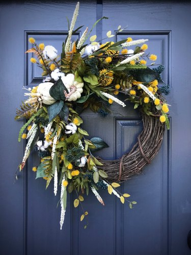 fall wreath made with grapevine, white pumpkins, yellow flowers, and greens