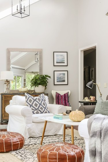 Fall decor idea for living room with rust-colored poufs, throw pillows, and neutral hues