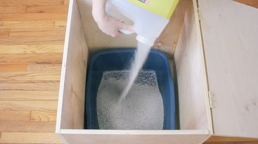 Pouring litter into litter pan inside plywood box