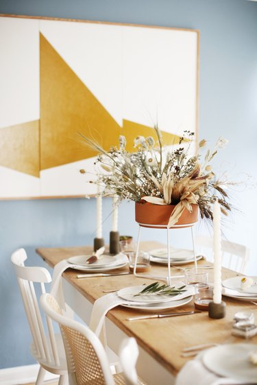 Dried floral fall centerpiece with terra cotta vase in modern dining room